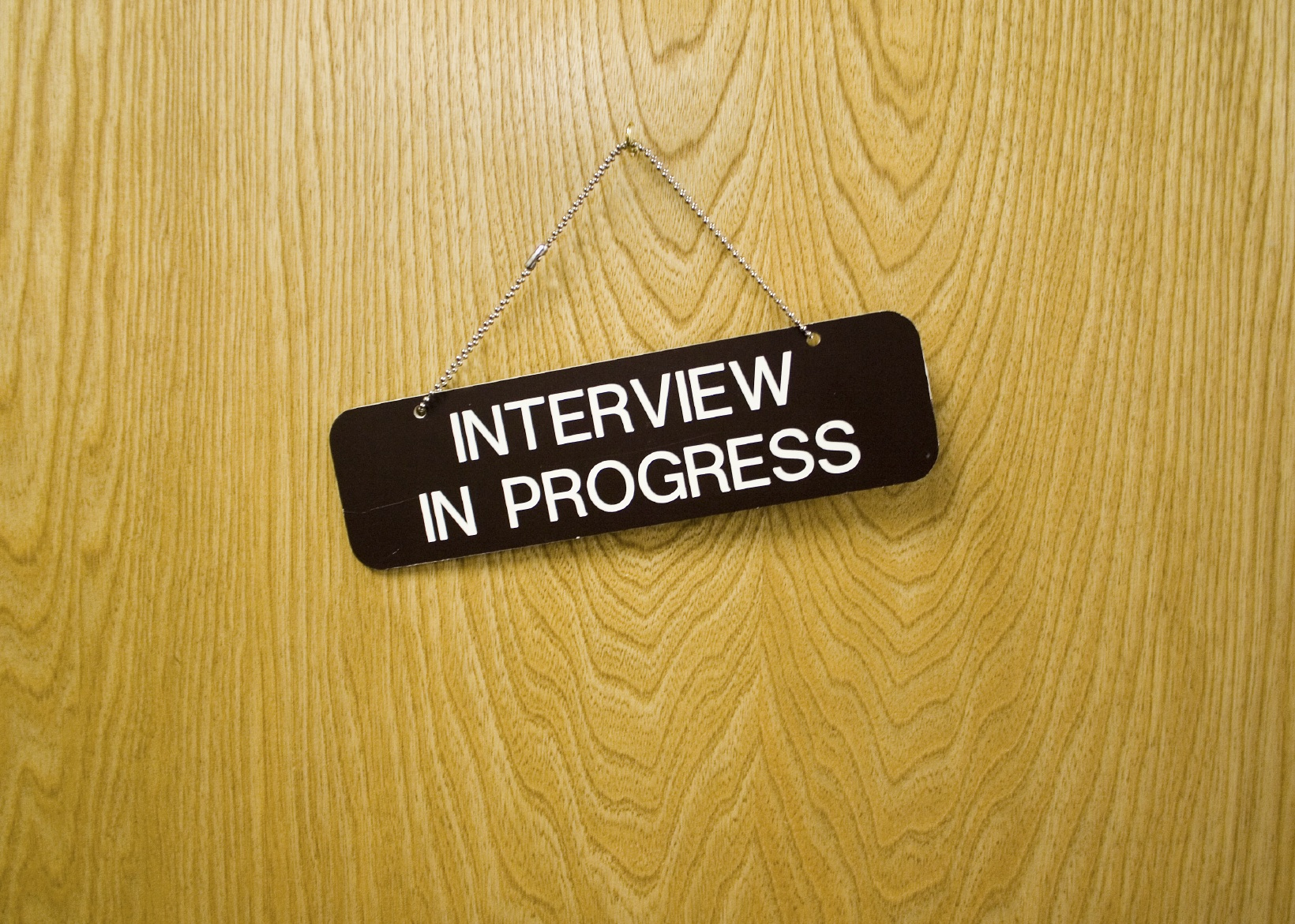 "Picture of a door with a sign on it that reads ""Interview in Progress"""