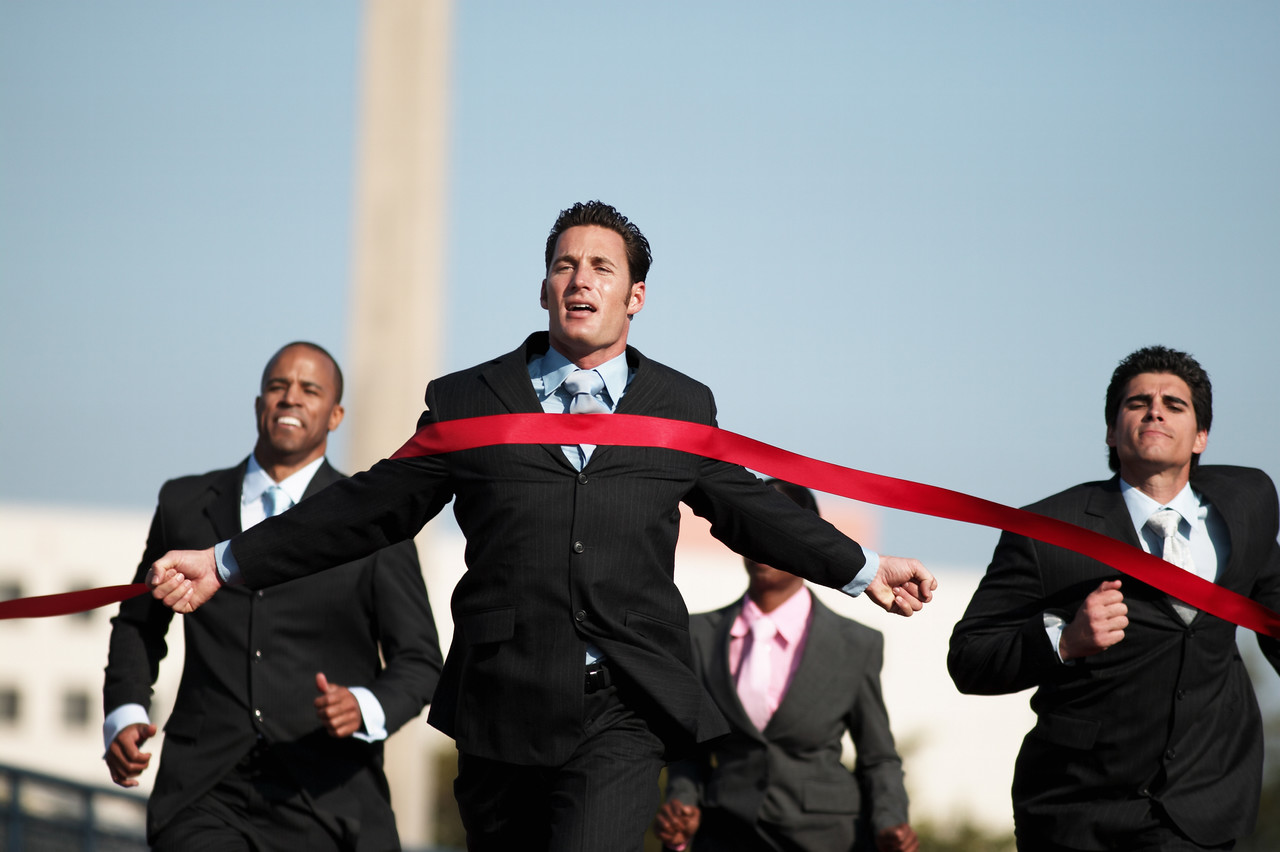Professionals in business attire running toward red finish line.